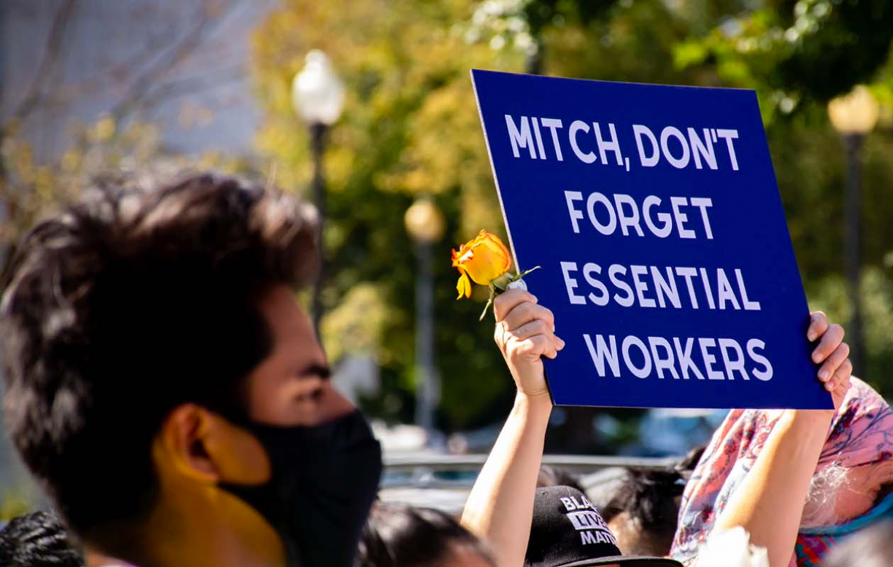 A photo of a man holding a sign in support of essential workers.